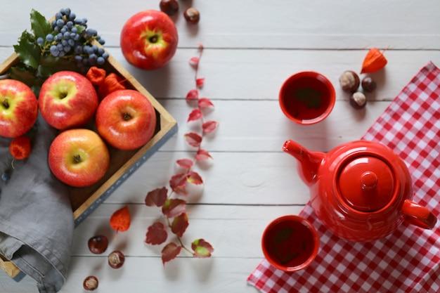 秋のお茶。青い木製の背景にお茶を一杯のティーポット