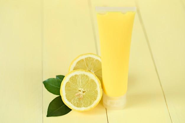 レモンエキス入り化粧品。黄色のシャワージェル、レモン抽出物と黄色のカットの新鮮なレモンのボディクリーム。