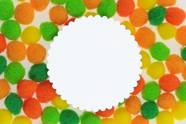 ポンポンの背景。オレンジ、黄色、緑の小さなポンポンの白いフレーム。コピースペース