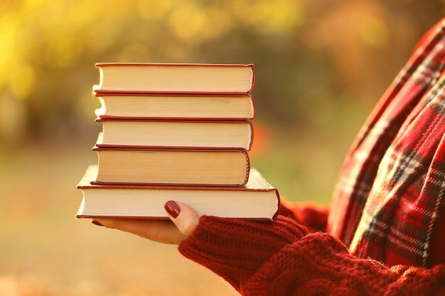 秋の本。秋の本を読んで。手で本のスタック。秋の時間。