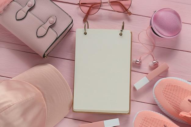 ピンクの木の板の背景にファッションアクセサリーと空のノートブック。