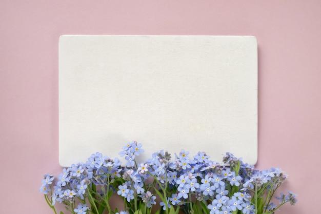 Цветы незабудки и белая карточка на розовом