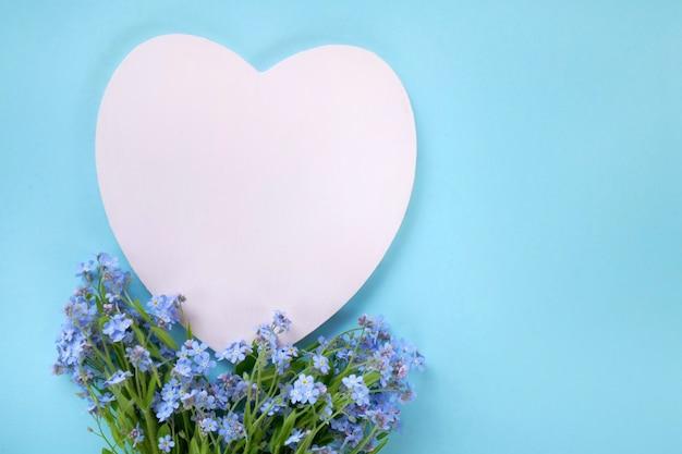 Цветочная открытка. цветы незабудки и розовое сердце пустым на пастельно-синем