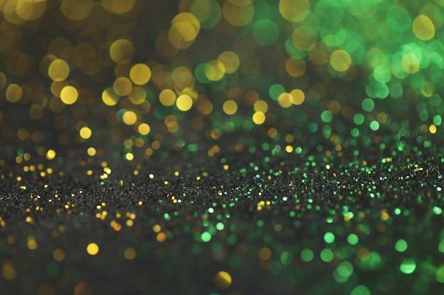 Золотой и зеленый блеск фон с блестящим боке