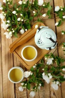 ジャスミン茶。オーガニックフラワーティーライトグリーンラウンドカップのジャスミンティー、ティーポット、ジャスミンの枝