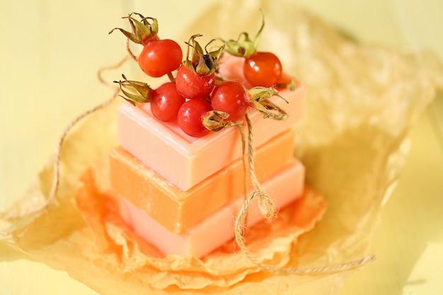 ローズヒップエキス入り石鹸。しわくちゃの黄色い紙にピンクとオレンジの天然オーガニック石鹸とワイルドローズベリー。ローズヒップの抽出物を使用したボディケアおよびフェイスケア製品