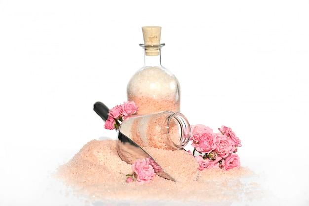 ローズエキス入りピンクシーソルト。ガラス瓶と唾液と新鮮なピンクのバラの入浴のためのローズエキスと塩。オーガニックボタニカルボディケア