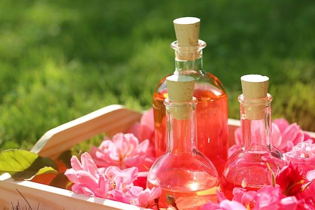ローズオイル。ローズ入りスパ。バラの花びら油。ガラスの瓶に天然のバラ油と木製のトレイにピンクのバラ。マッサージ、アロマセラピー、オーガニック化粧品のコンセプト