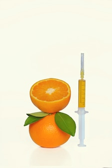 Сыворотка с витамином с в шприце и апельсин с листьями