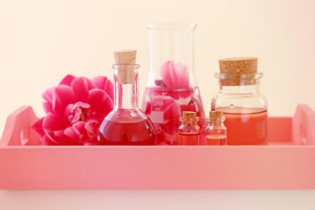 ローズオイル。ローズ入りスパ。バラの花びらの油、ガラス瓶の中のバラの水。