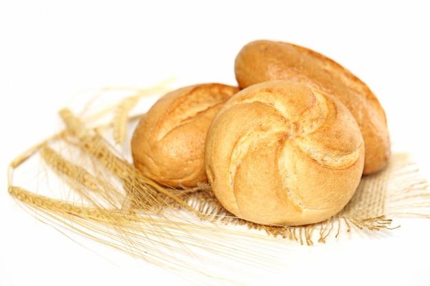 Свежие булочки на мешковине и колосья пшеницы на белой поверхности