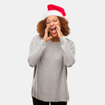 Молодая чернокожая женщина в шляпе санта, крича что-то счастливое на фронт