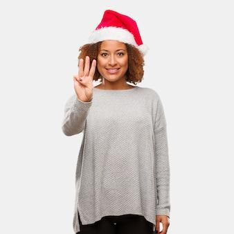 Молодая чернокожая женщина в шляпе санта показывает номер три