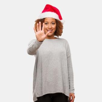 Молодая чернокожая женщина в шляпе санта показывает номер пять