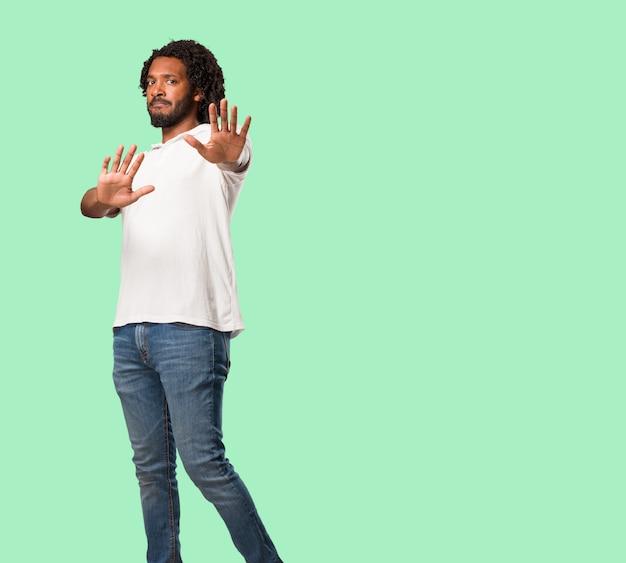 ハンサムなアフリカ系アメリカ人、深刻で決心した、手を前に置く、ジェスチャーを止める、概念を否定する