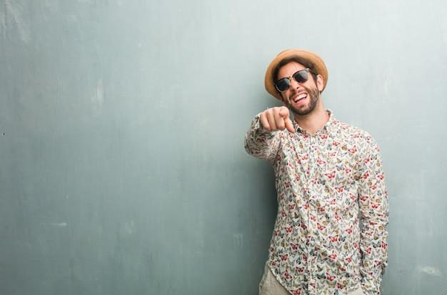 カラフルなシャツを着て、笑って、別のものを楽しんでいる若い旅行者の男
