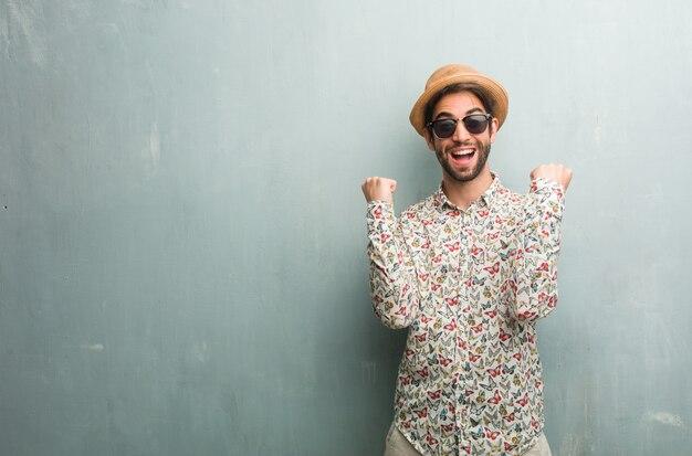 カラフルなシャツを着ている若い旅行者の男は、とても幸せで興奮して、腕を上げる