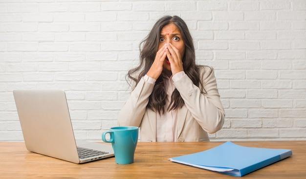 Молодая индийская женщина в офисе очень напугана и напугана, отчаянно чего-то хочет