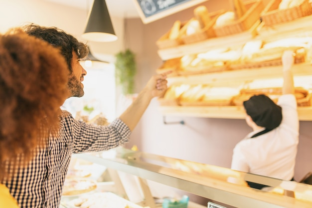 ベーカリーで若いモダンカップル、パンを選ぶ