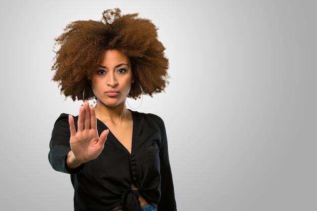 Афро женщина делает символ остановки