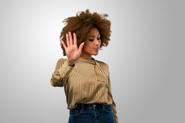 Афро женщина делает жест остановки