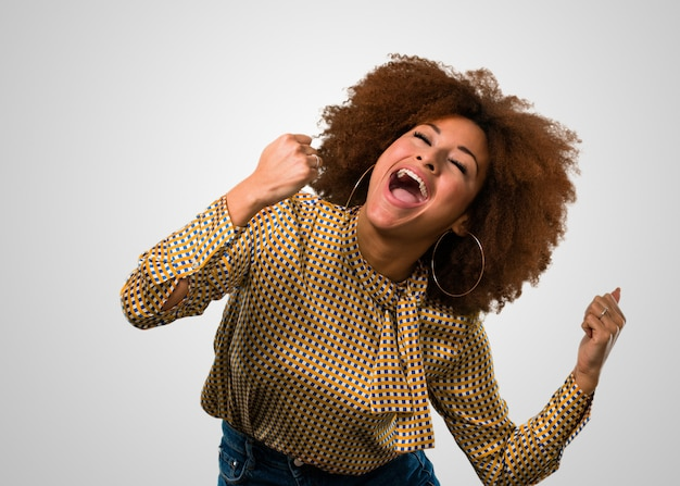 Афро женщина празднует счастливы и веселы