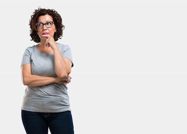 Среднего возраста женщина сомневается и смущается, думает об идее или о чем-то беспокоится
