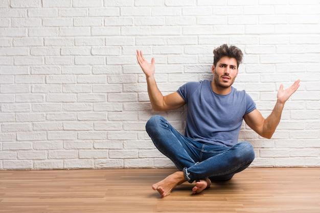 若い自然の男は、木製の床に座って狂っていると絶望的な、コントロールから悲鳴を上げる