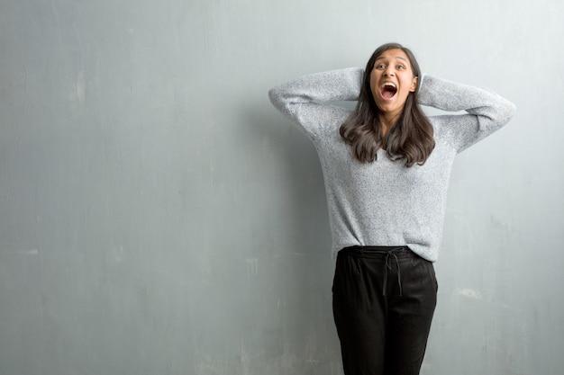 グランジの壁に対して若いインド人女性は驚いてショックを受けて、広い目で見