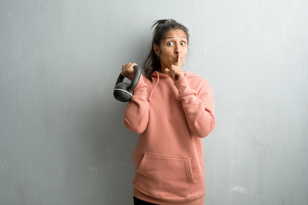 秘密を守るか沈黙を求めて壁にスポーティな若いインド人女性