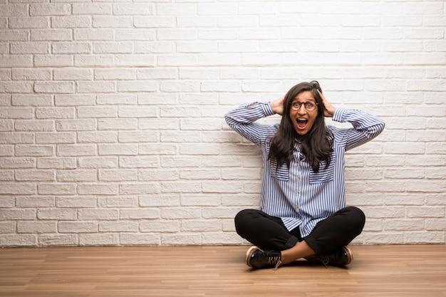 若いインド人女性は驚いてショックを受けて、広い目で見てレンガの壁に座る。