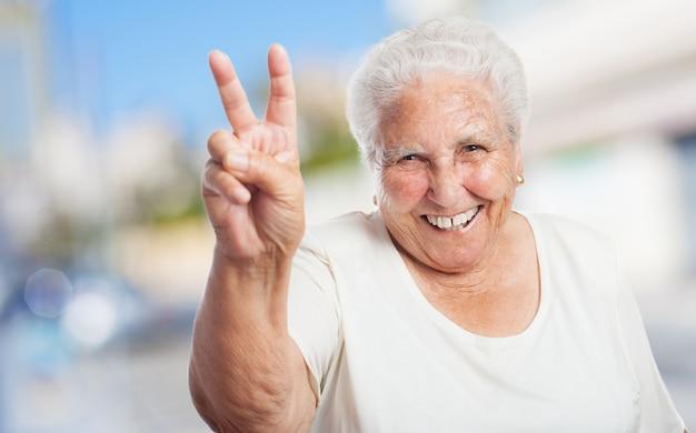 Бабушка с двумя пальцами поднял и улыбается