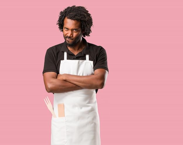 ハンサムなアフリカ系アメリカ人のパン屋は非常に怒って動揺して、非常に緊張して、激怒して叫んで