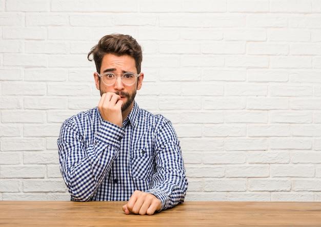 痛烈な爪を座っている若い白人男性、緊張し、非常に心配しているし、未来のために怖い