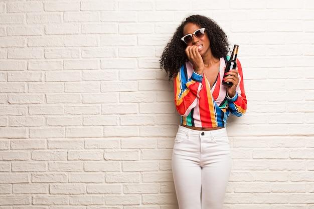 若い黒人女性の爪をかむ、緊張し、非常に心配し、将来を恐れて