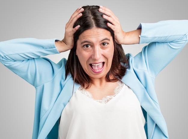 中年の女性が驚いてショックを受けて、広い目で見て、申し出によってまたはによって