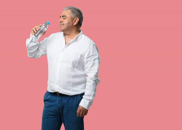 Мужчина средних лет улыбается, довольный, держит бутылку холодной воды