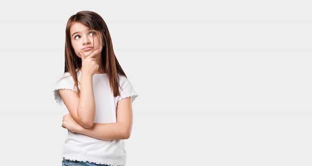 Маленькая девочка всего тела думает и смотрит вверх, смущенная идеей