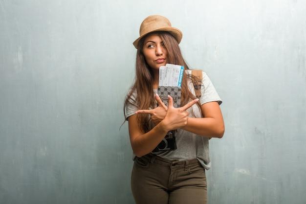混乱して疑わしい壁に対して若い旅行者ラテン女性の肖像画
