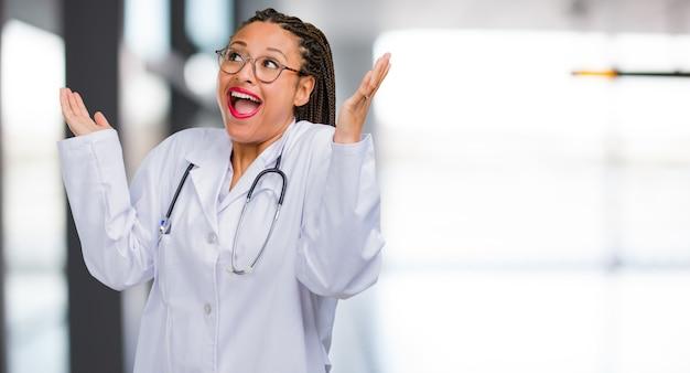 Портрет молодой женщины чернокожего доктора смеется и веселится, будучи расслабленным и веселым