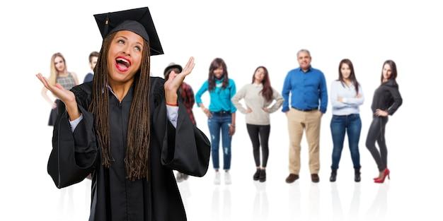 笑いと楽しんでお下げを着て若い卒業黒人女性