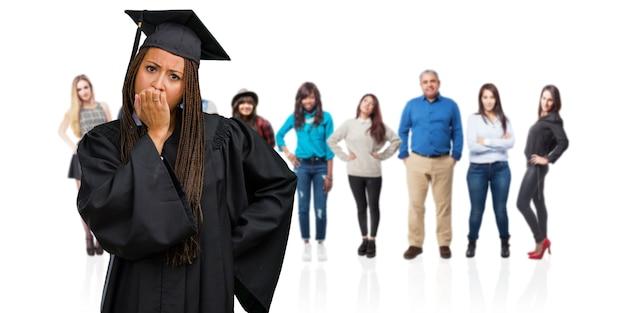 爪をかむ、神経質で非常に心配しているお下げを着ている若い卒業黒人女性