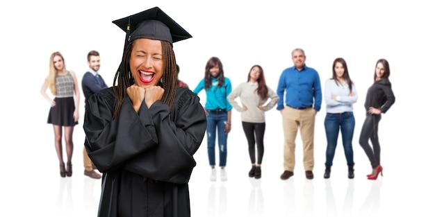 非常に幸せで興奮して、腕を上げてお下げを身に着けている若い卒業黒人女性