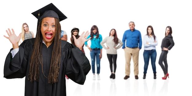 オファーやプロに驚いた幸せ、叫んでお下げを身に着けている若い卒業黒人女性