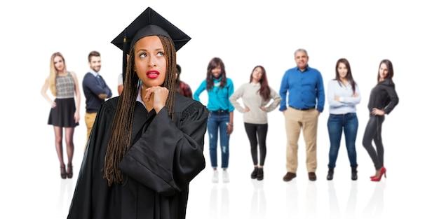 考えを見上げて、考えについて混乱しているお下げを着ている若い卒業黒人女性
