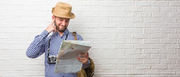 バックパックと手で耳を覆っているビンテージカメラを身に着けている若い旅行者男