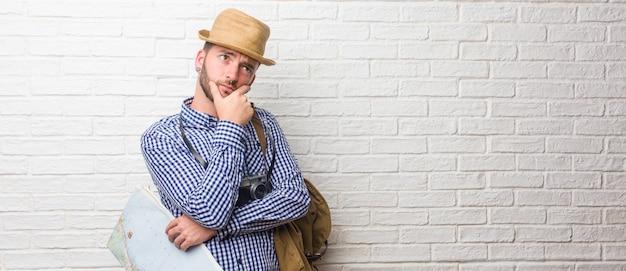 バックパックとビンテージカメラ疑いと混乱を着ている若い旅行者男