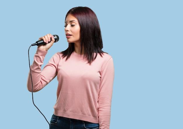 幸せでやる気の若いきれいな女性、マイクで歌を歌う