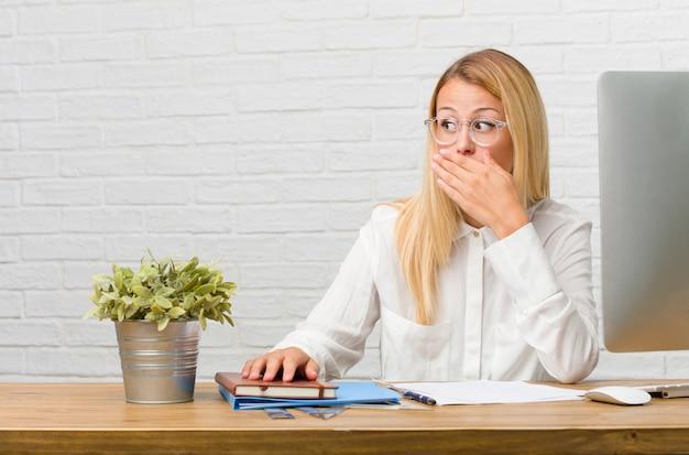 Портрет молодого студента сидя на ее столе делая задачи покрывая рот.