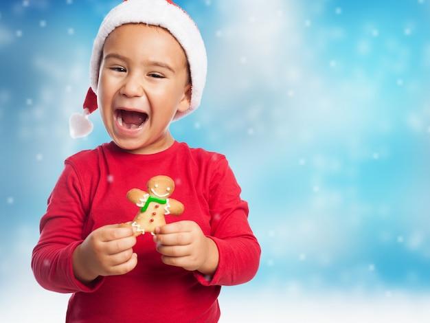 クリスマスの帽子とジンジャーブレッドを持つキッド